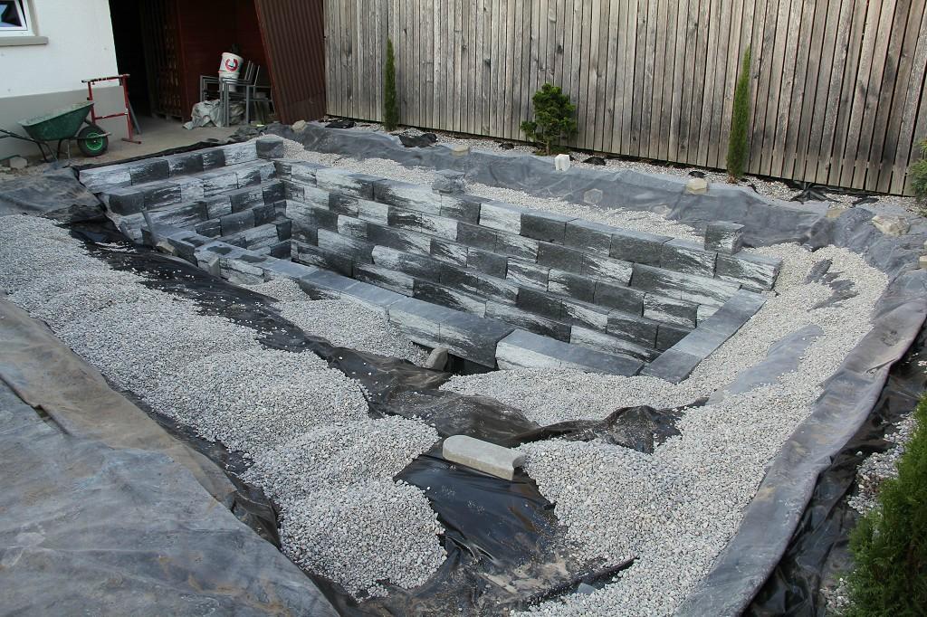 con grandes rocas de color oscuro crearon los muros del estanque y una escalera de acceso with suelos para jardin baratos
