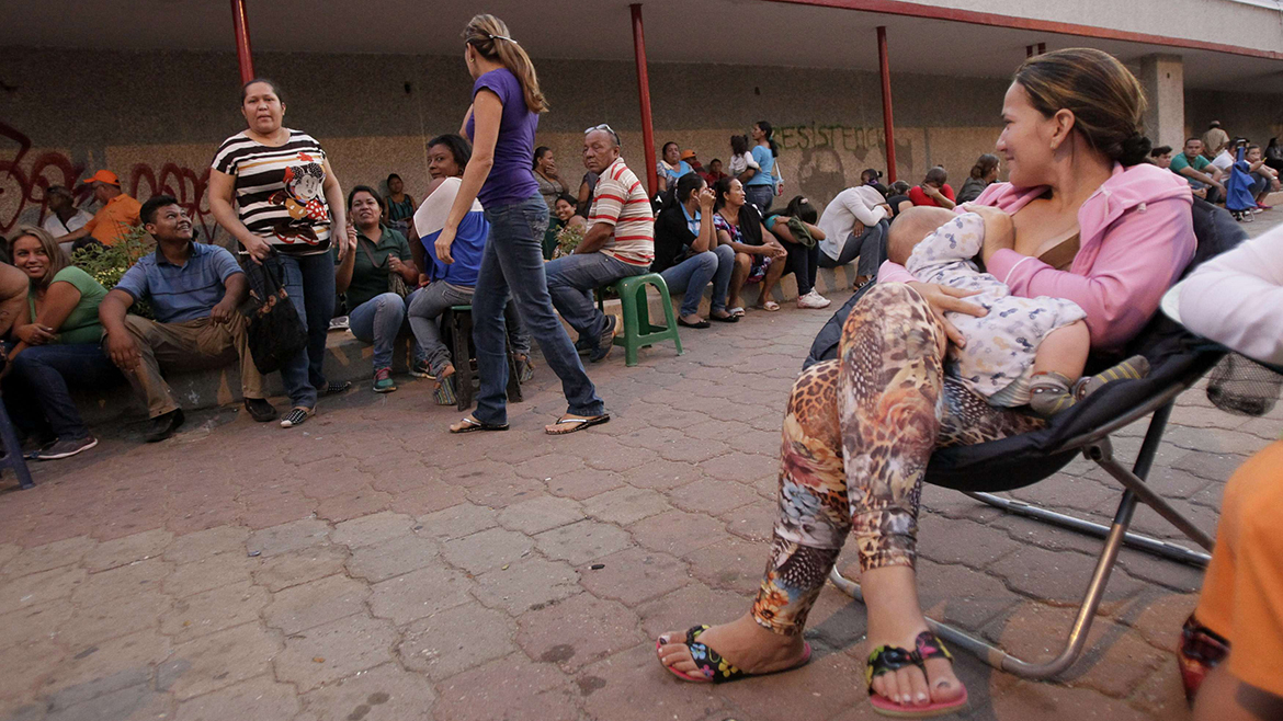 People wait before sunrise to enter the state-run Bicentenario supermarket in Maracaibo