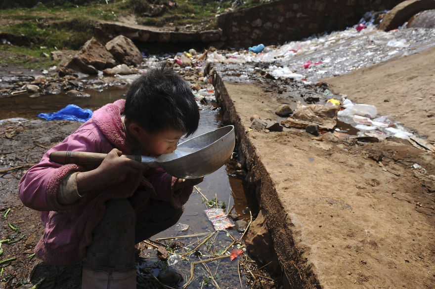 A child drinks water near a stream in Fuyuan county