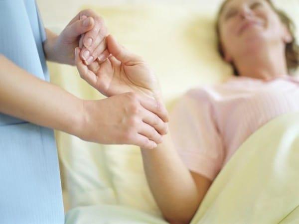 Nurse checking female patient's pulse on wrist, close-up