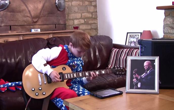 chico joven toca guitarra