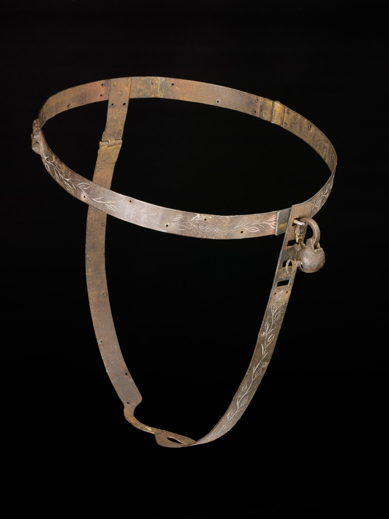 UNITED KINGDOM - SEPTEMBER 20: Iron chastity belt complete with padlock. Iron chastity belt complete with padlock. Front view of whole obejct against black background. (Photo by Science & Society Picture Library/SSPL/Getty Images)