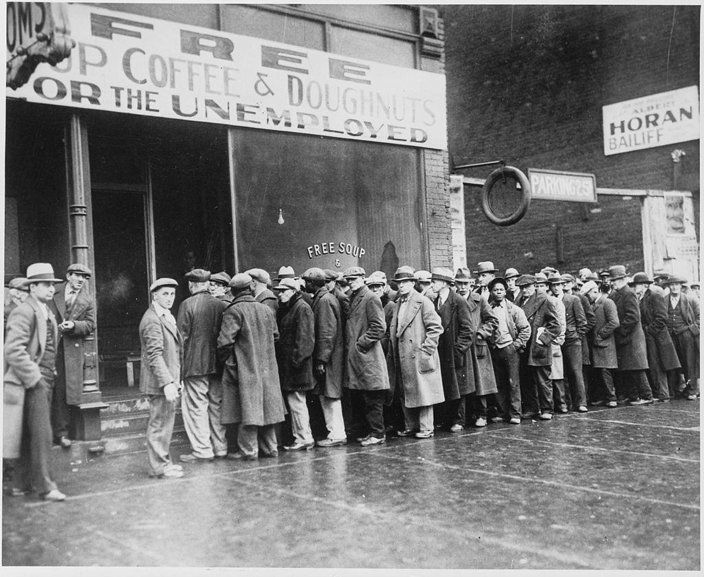 Parados hacen cola para recibir comida en una de las cocinas de Al Capone.
