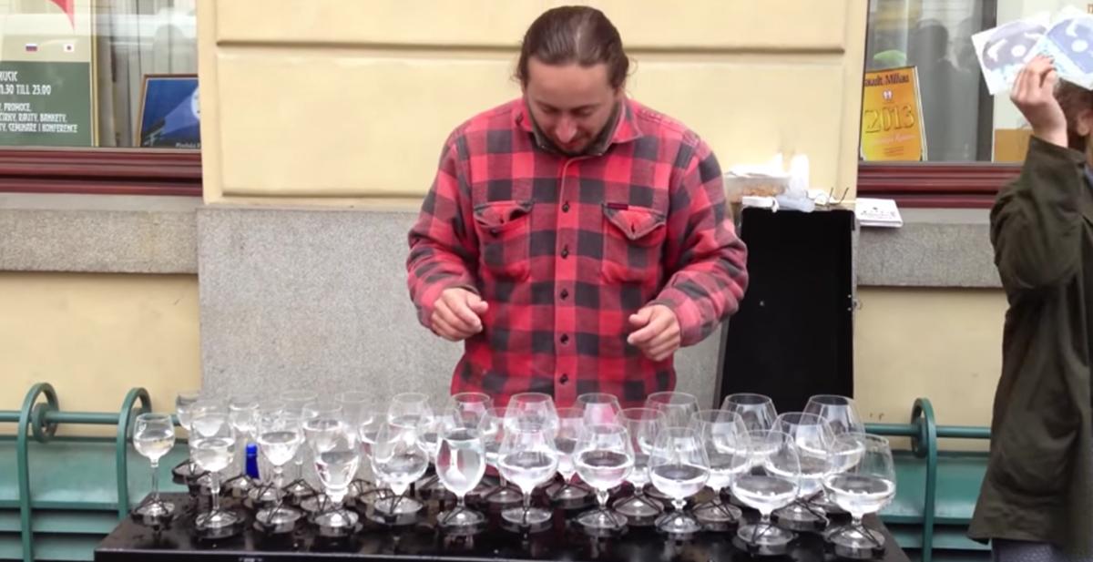 Señor haciendo musica con copas con agua