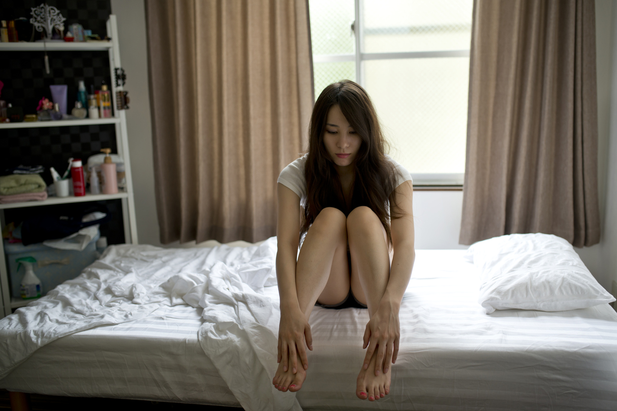Beautiful girl sitting pensively holding her legs in bedroom.