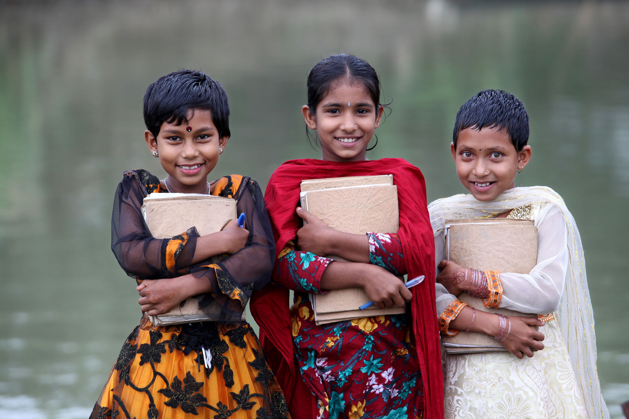 Three girls smile while standing in front of the open deck holding their books at the boat school, Shanto Nagar, Singara, Natore. 03 November 2012. Photo: Abir Abdullah/SSS