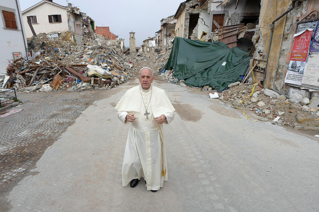 "Pope Francis stands in front of rubble, with the standing bell tower in the background, of the quake-struck town of Amatrice, Italy, Tuesday, Oct. 4, 2016. Francis had made clear his intentions to visit the August quake-stricken zone in central Italy, but without announcing a date, indicating that he wanted to go alone ""to be close to the people."" (L'Osservatore Romano/ Pool Photo via AP)"