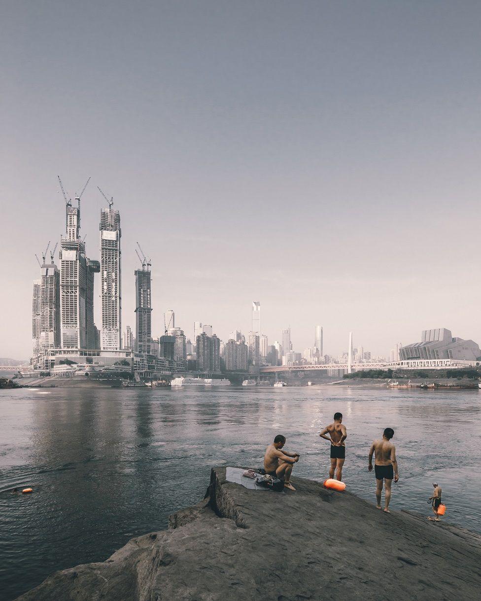 Concurso foto arquitectura. Nadadores en la orilla del río frente a la construcción de Raffles City, en Chongqing (China)