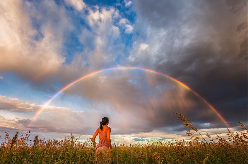 mujer posando con un arcoiris en un prado