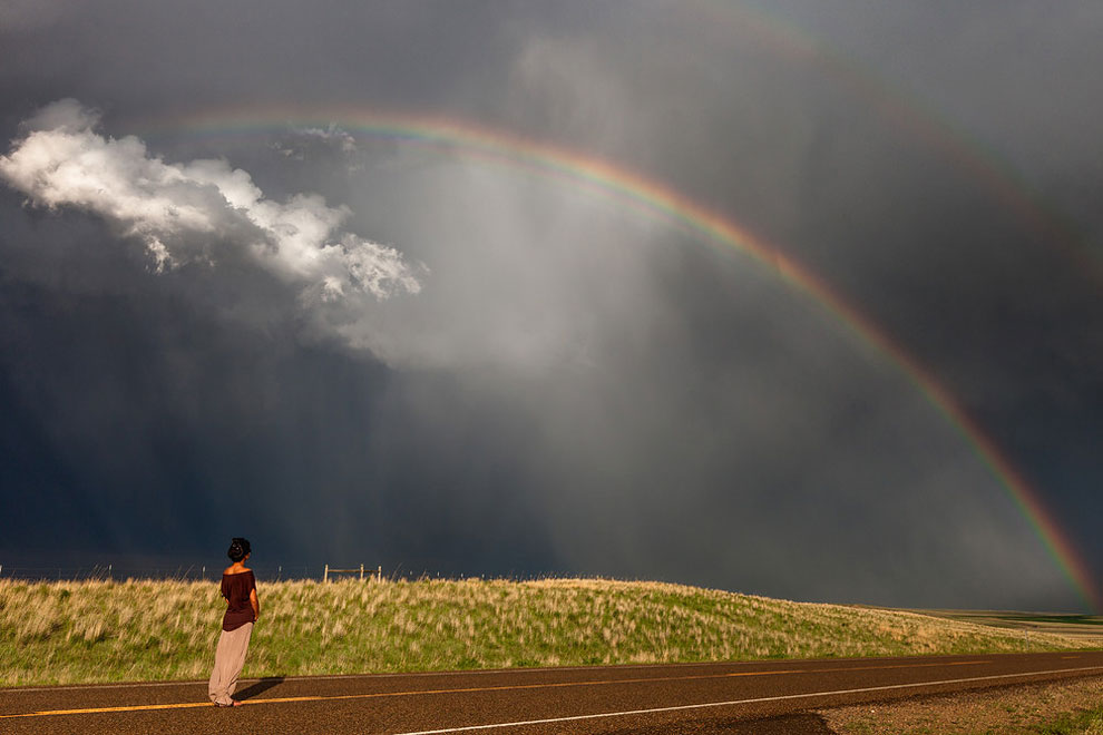 mujer junto a arcoiris y nubes
