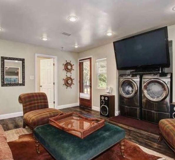 salón de una casa con lavadoras bajo la televisión