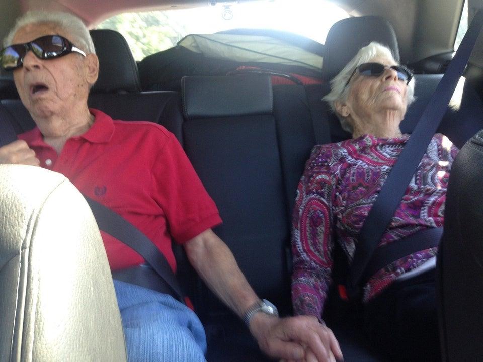 abuelos dándose la mano en el coche