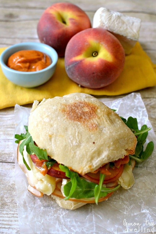 sandwich de pavo, queso brie, duraznos y rúcula
