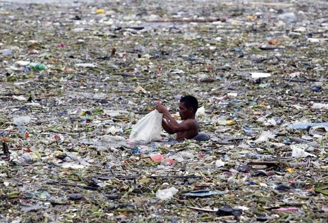 hombre nadando entre plasticos