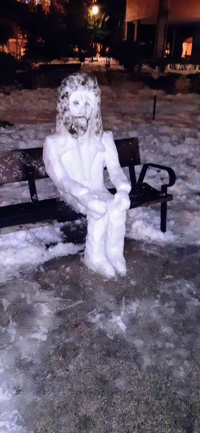hombre de nieve sentado en banco