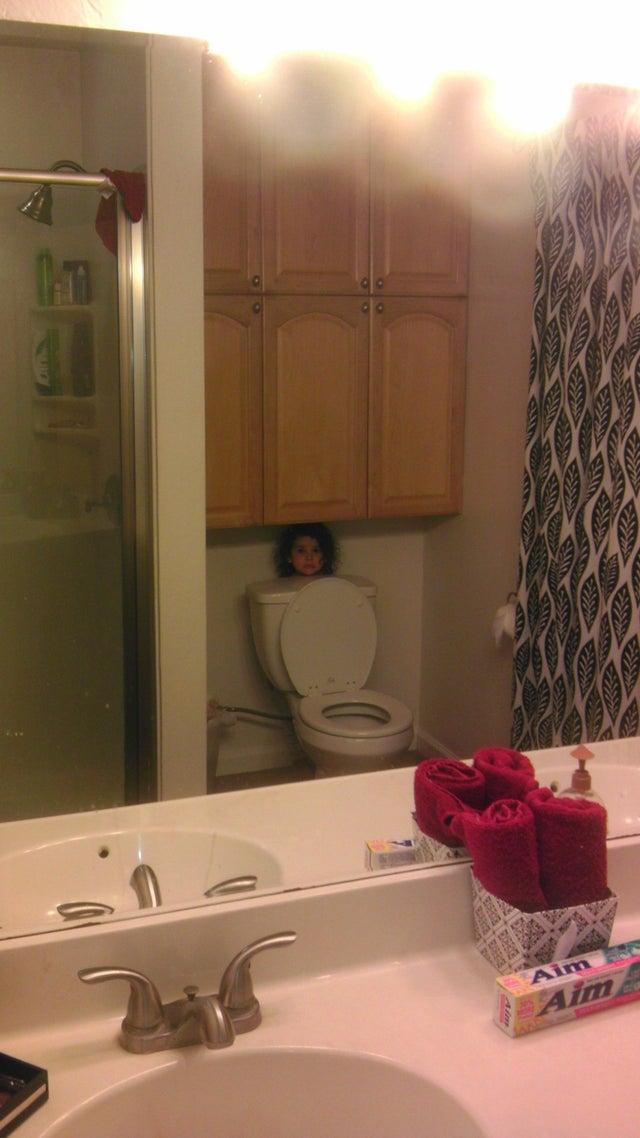 niñas escondida tras el inodoro