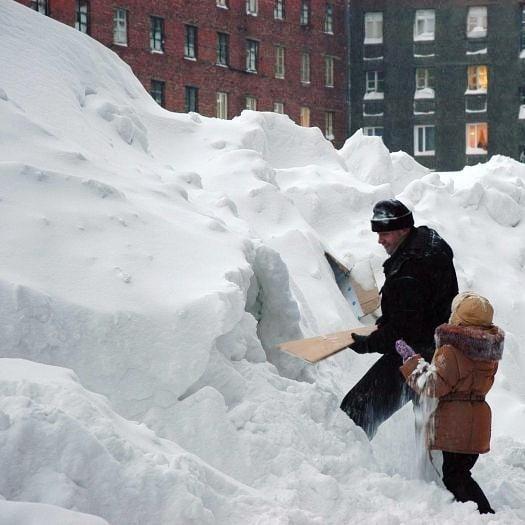 padre e hija quitando nieve