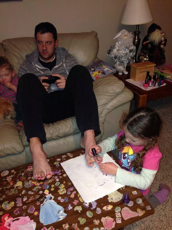 niña pintando las uñas de los pies a su padre