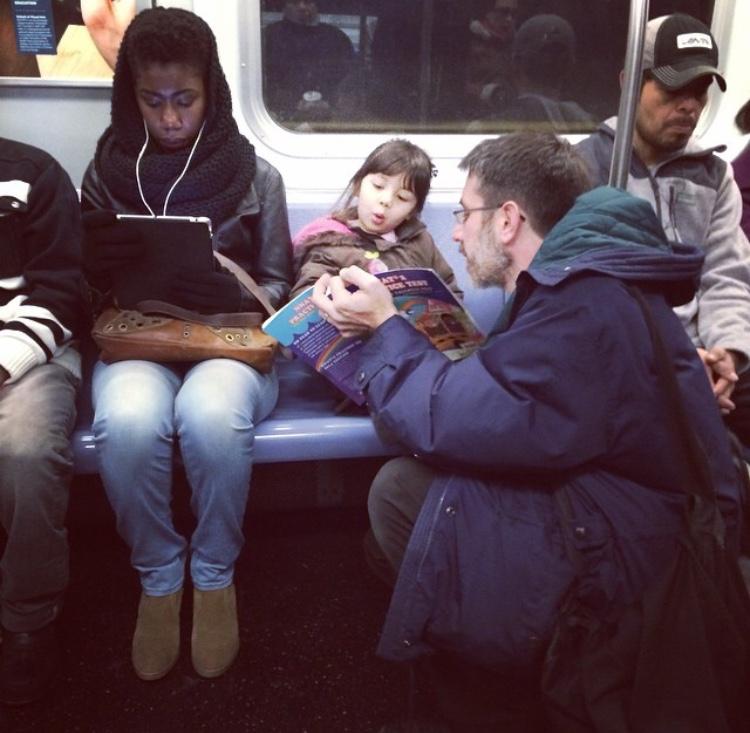 padre hace la tarea con su hija en el metro