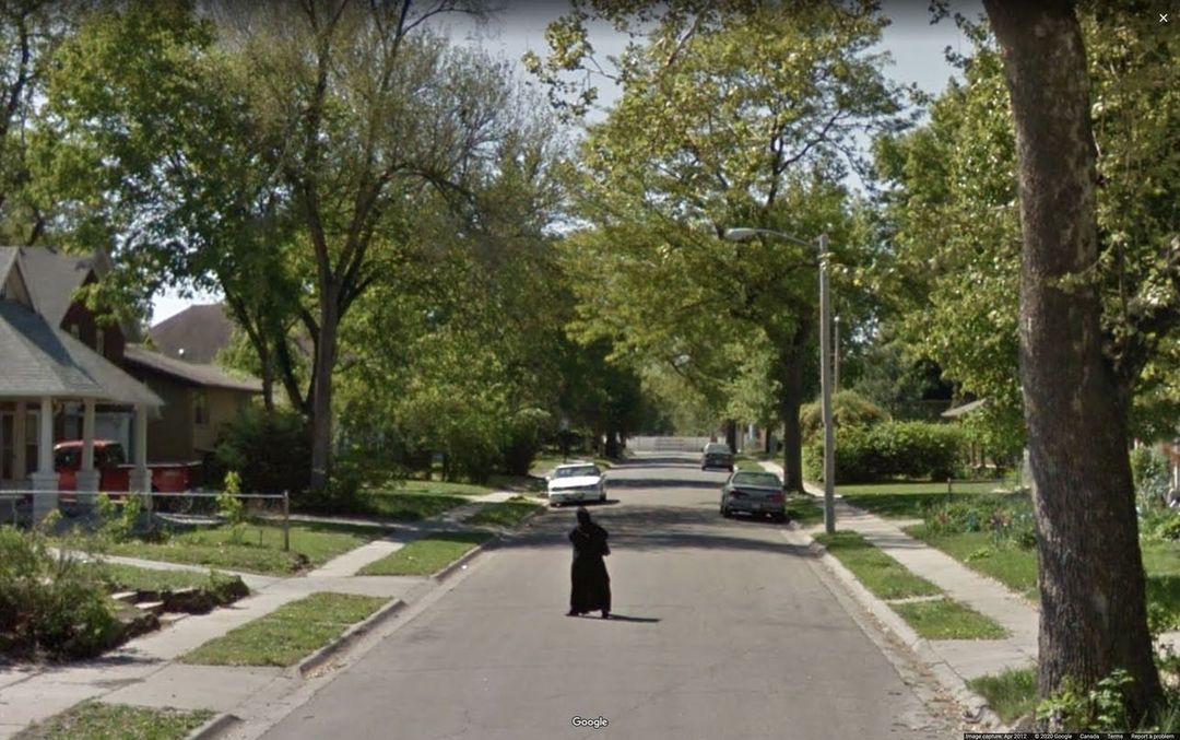 hombre vestido de negro en mitad de la calle